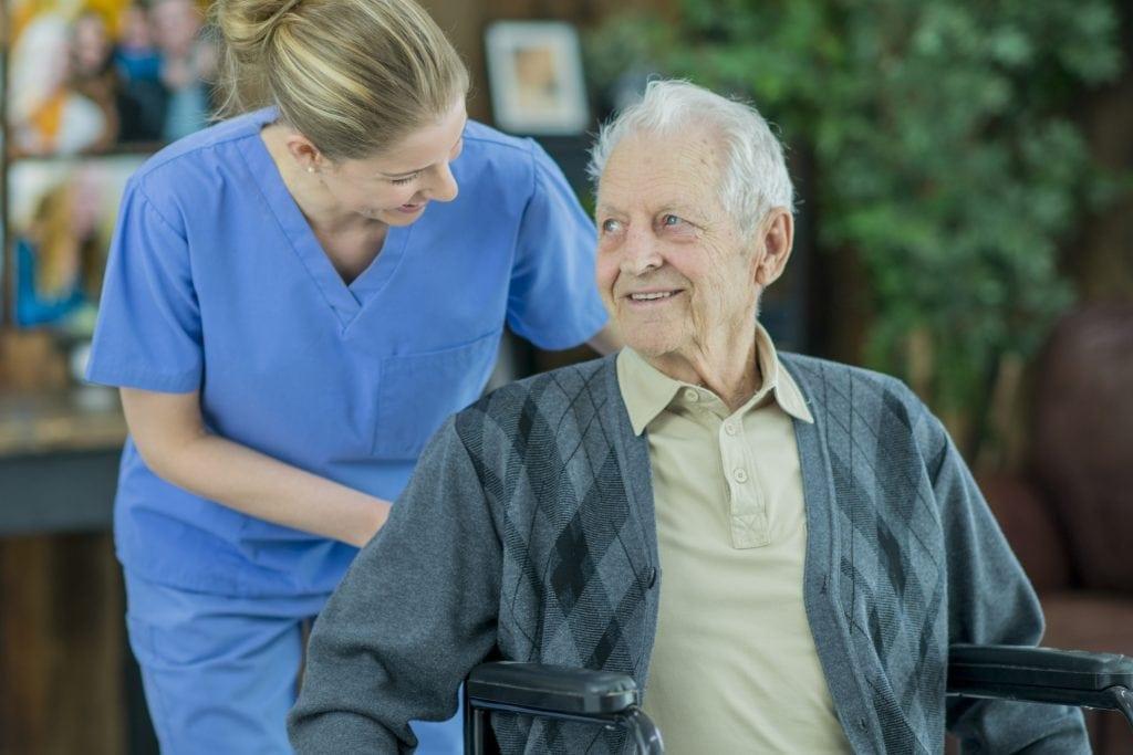 Nurse Pushing Elderly Man In Wheelchair