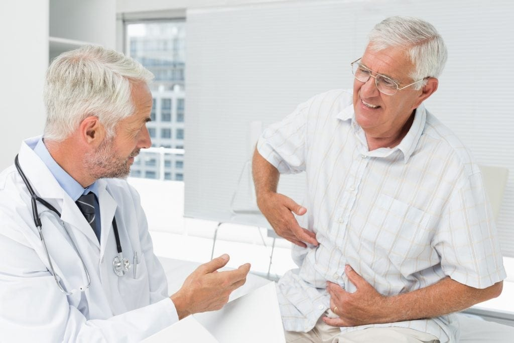 Patient Pointing To Abdomen At Doctor's Office