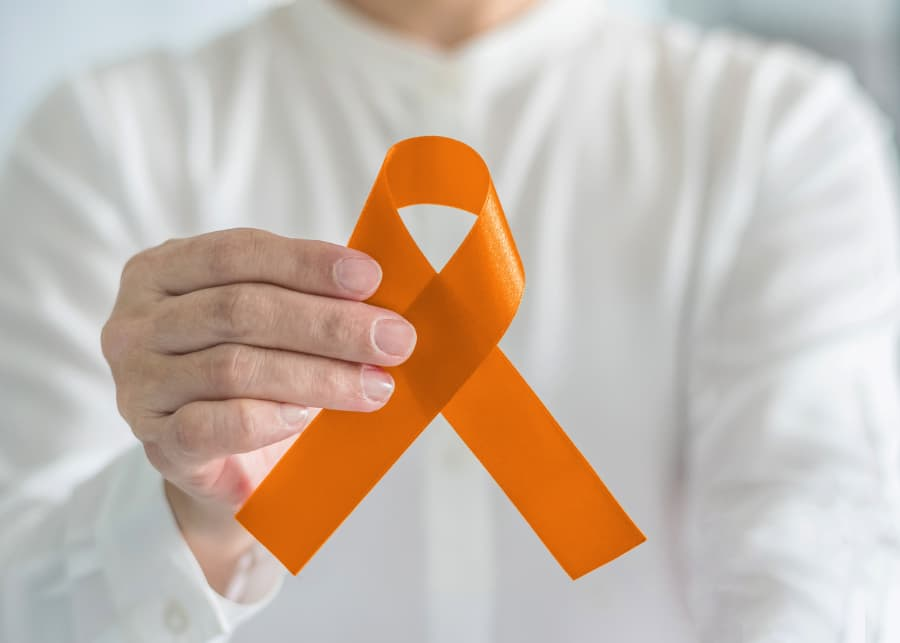 Person holding orange cancer ribbon